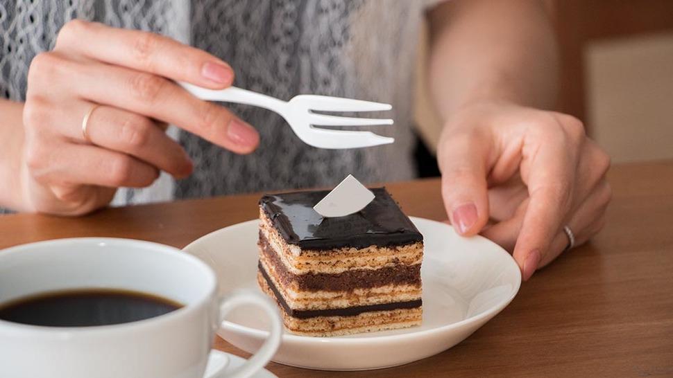 ケーキフォークで今にもケーキに切れ目をつけようとしている様子