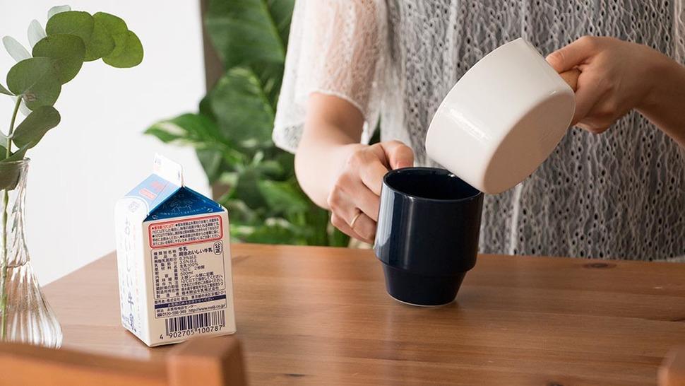ミルクパンでコーヒーカップに液体を注いでいる様子