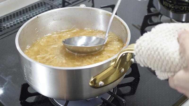 プロキング 浅型片手ソテー鍋(18cm)で布巾を使用している様子