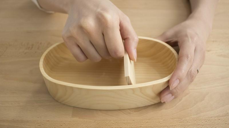 紀州ひのきの弁当箱(小)にしきりを入れている様子